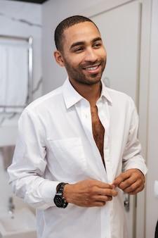 Vertikales porträt des lächelnden afrikanischen mannes im hemd wäscht im badezimmer im hotel