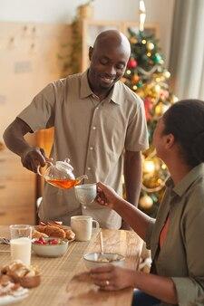 Vertikales porträt des lächelnden afroamerikanischen mannes, der tee für frau gießt, während weihnachtsessen zu hause genießt