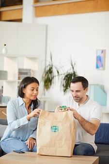 Vertikales porträt des mannes und der frau, die nahrungsmittellieferbeutel öffnen, während mittagessen zum mitnehmen im büro genießen