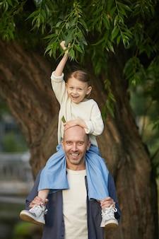 Vertikales porträt des niedlichen kleinen mädchens, das glücklich lacht, während es auf den schultern seines vaters sitzt und den spaziergang im park genießt