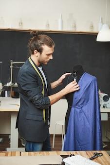 Vertikales porträt des reifen attraktiven talentierten hispanischen kleidungsdesigners, der blaues kleid für das nähen vorbereitet, fehler auf mannequin beseitigt, sich für modenschau bereit macht