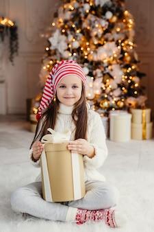 Vertikales porträt des schönen angenehmen schauenden kleinen kindes trägt gestrickte strickjacke und socken, sitzt gekreuzte beine mit geschenk, hat den wunsch, es einzuwickeln und ist im wohnzimmer nahe verziertem baum des neuen jahres