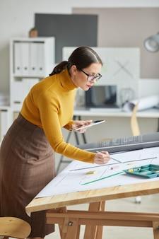 Vertikales porträt des weiblichen architekten, der blaupausen beim arbeiten am schreibtisch im büro zeichnet,