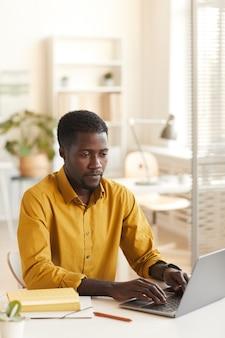 Vertikales porträt des zeitgenössischen afroamerikanischen mannes unter verwendung des laptops beim sitzen am weißen schreibtisch im büro, kopierraum oben