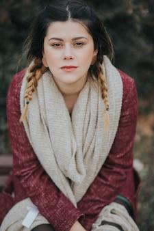 Vertikales porträt einer brünetten jungen dame mit schal und mantel im wald am herbst