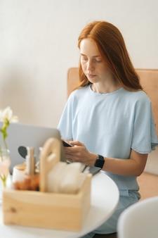 Vertikales porträt einer fokussierten jungen frau in intelligenter uhr mit laptop und telefon, die am tisch im café mit warmem tageslicht, selektivem fokus sitzt. hübsche rothaarige dame, die drinnen arbeitet oder studiert.