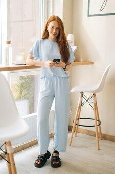 Vertikales porträt einer fröhlichen, attraktiven jungen frau, die smartphone verwendet und online-nachrichten am fenster im café eingibt. kaukasische dame der hübschen rothaarigen, die freizeitbeschäftigung im café hat.