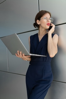Vertikales porträt einer geschäftsfrau. spricht am telefon, hält einen laptop in den händen und schaut zur seite. auf aluminiumwand geschossen