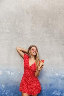 Vertikales porträt einer glücklichen frau essen eis auf straßen der stadt während des sommerspaziergangs, lehnt sich an die wand und lächelt glücklich, sonnenbrille mit rotem kleid tragend