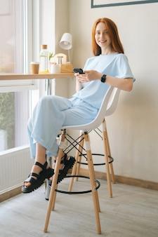 Vertikales porträt einer glücklichen jungen frau in freizeitkleidung, die handy am schreibtisch am fenster in einem gemütlichen hellen café hält. kaukasische dame der hübschen rothaarigen, die freizeitbeschäftigung im café hat.
