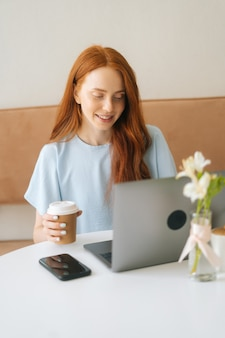 Vertikales porträt einer glücklichen jungen schönen frau, die auf dem laptop tippt und kaffee aus der tasse trinkt, während sie im gemütlichen café aus der ferne arbeitet. hübsche kaukasische dame der rothaarigen entfernt, die arbeitet oder studiert.