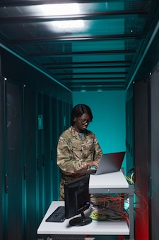 Vertikales porträt einer jungen afroamerikanischen frau in militäruniform mit computer beim einrichten des netzwerks im serverraum