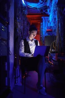 Vertikales porträt einer jungen technikerin, die ein internetnetzwerk im serverraum einrichtet