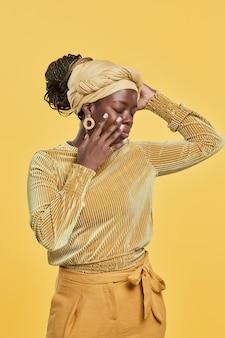 Vertikales porträt einer trendigen afroamerikanischen frau mit kopftuch und ethnischem schmuck beim tanzen...
