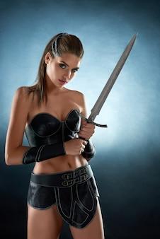 Vertikales porträt einer wunderschönen weiblichen amazonas-kriegerin mit einem selbstbewussten und aggressiven schwertkämpfer.