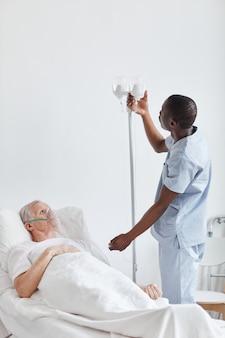 Vertikales porträt eines afroamerikanischen krankenpflegers, der einen infusionstropfen einrichtet, während er einen älteren mann im krankenhausbett behandelt