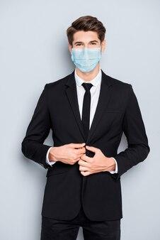 Vertikales porträt eines attraktiven, luxuriösen, eleganten, gesunden finanziers mit blauer gaze-maske zur fixierung des knopfes cov ncov mers influenza-präventions-sicherheitspflege einzeln auf grauem hintergrund