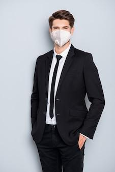 Vertikales porträt eines attraktiven, schicken, eleganten, gesunden kerls mit n95-weißer atemschutzmaske cov ncov mers influenza-sicherheitspflege einzeln auf grauem hintergrund