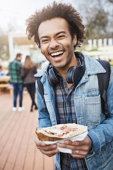 Vertikales porträt eines charmanten, nicht rasierten, dunkelhäutigen mannes, der ein leckeres sandwich hält, während er mit einem rucksack im park spazieren geht oder an einem lebensmittelfest teilnimmt, laut lacht und gute laune ausdrückt