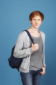 Vertikales porträt eines ernsthaften jungen rothaarigen männlichen studenten im lässigen grauen outfit mit schwarzem rucksack, hand in der tasche haltend, mit entspanntem und selbstbewusstem ausdruck