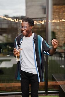 Vertikales porträt eines jungen afroamerikaners, der ein getränk hält, während er eine party im freien auf dem dach genießt