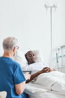 Vertikales porträt eines jungen afroamerikaners, der im krankenhaus liegt und mit dem leitenden arzt spricht