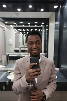Vertikales porträt eines jungen afroamerikanischen geschäftsmannes, der spiegel-selfie in der öffentlichen toilette macht