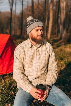 Vertikales porträt eines jungen bärtigen hipsters sitzt vor seinem zelt im wald.