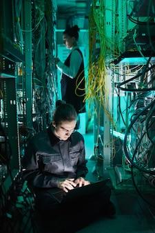 Vertikales porträt eines jungen technikers, der ein computernetzwerk im serverraum einrichtet
