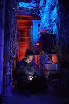Vertikales porträt eines jungen technikers, der ein internetnetzwerk im serverraum einrichtet