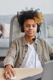 Vertikales porträt eines lächelnden afroamerikanischen jungen, der ein headset trägt, während er zu hause einen laptop benutzt und in die kamera schaut