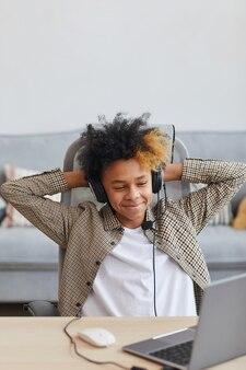 Vertikales porträt eines lächelnden afroamerikanischen jungen mit headset, der sich im stuhl entspannt, während er zu hause einen laptop verwendet