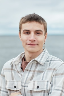 Vertikales porträt eines lächelnden jungen mannes, der die kamera am strand mit himmel im hintergrund betrachtet