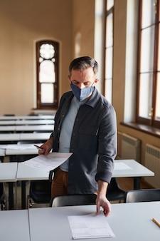 Vertikales porträt eines reifen college-professors, der eine maske trägt, während er prüfungsunterlagen in der von sonnenlicht beleuchteten schulaula auslegt