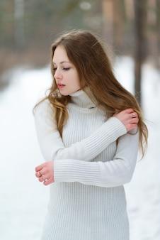 Vertikales porträt eines schönen jungen mädchens in einem weißen pullover gegen den winterwald