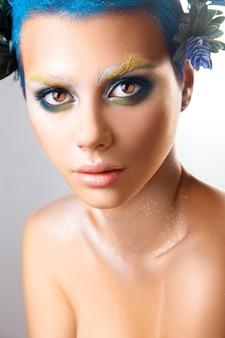Vertikales porträt eines schönen mädchens mit mehrfarbigem make-up und blauem haar studioaufnahme isoliert