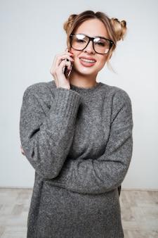 Vertikales porträt frau im pullover und in den brillen, die am telefon sprechen