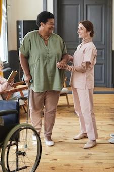 Vertikales porträt in voller länge einer lächelnden jungen frau, die senioren im modernen altersheim hilft