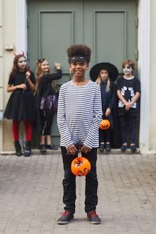 Vertikales porträt in voller länge einer multiethnischen gruppe von kindern, die halloween-kostüme tragen, während sie zusammen süßes oder saures tun, konzentrieren sich auf den afroamerikanischen jungen im vordergrund