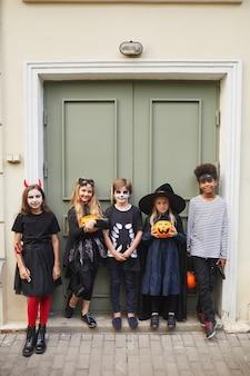 Vertikales porträt in voller länge einer multiethnischen gruppe von kindern, die halloween-kostüme tragen, während süßes oder saures zusammen