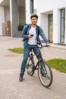 Vertikales porträt in voller länge eines fröhlichen männlichen kuriers mit rucksack, der mit fahrrad in der stadtstraße steht und die navigations-app am telefon verwendet. lieferbote, der nach der kundenadresse sucht, die smartphone sucht.