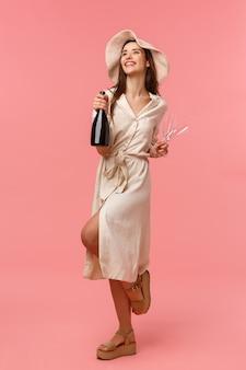 Vertikales porträt in voller länge, festlich, fröhlich und sorglos, wunderschöne, weibliche frau im urlaub, freizeit genießen, spaß mit freundinnen haben, party schmeißen, flasche champagner und gläser halten