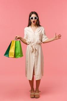 Vertikales porträt in voller länge überraschtes und aufgeregtes attraktives weibliches mädchen im kleid und in der sonnenbrille, einkaufstaschen halten, jemanden im speicher sehend und keuchen überrascht und stehen rosa