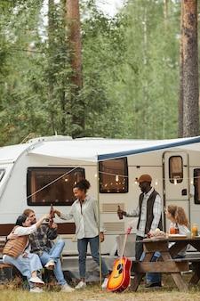 Vertikales porträt in voller länge von freunden, die beim camping mit van im waldkopierraum im freien genießen