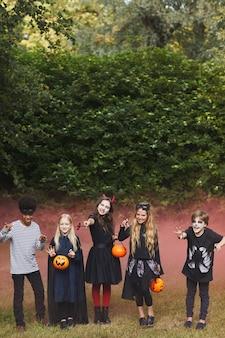 Vertikales porträt in voller länge von gruseligen kindern, die halloween-kostüme im freien mit farbigem rotem rauch in der oberfläche tragen, kopieren raum
