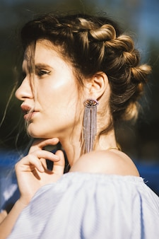 Vertikales porträt mit flachem fokus eines attraktiven weiblichen modells, das ihr kinn berührt