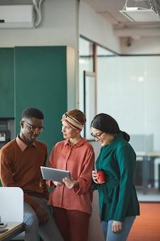 Vertikales porträt von drei zeitgenössischen geschäftsleuten, die arbeit im büro besprechen, fokus auf junge frau halten tablette halten und mit kollegen sprechen, raum kopieren