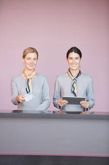 Vertikales porträt von zwei lächelnden flugbegleitern, die dem passagier tickets beim stehen am check-in-schalter im flughafen übergeben,