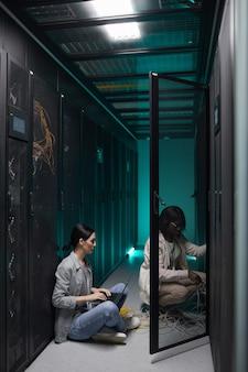 Vertikales porträt von zwei weiblichen dateningenieuren, die laptop im serverraum verwenden und supercomputernetzwerk einrichten, platz kopieren
