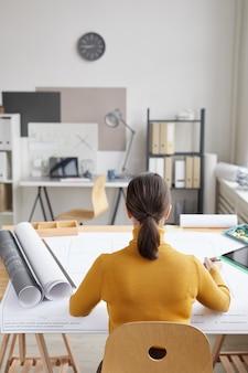Vertikales rückansichtporträt des weiblichen architekten, der blaupausen beim sitzen am schreibtisch im büro zeichnet